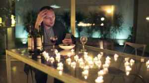 stock-footage-sad-lonely-romantic-man-waiting-for-his-date-by-the-table-at-home