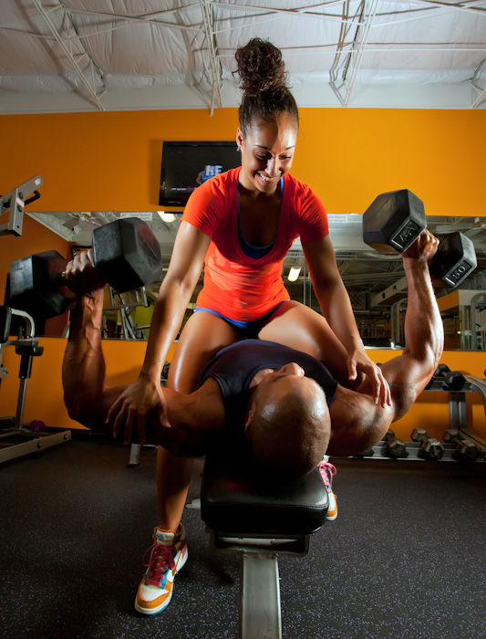Young Woman and Man working out together in a Gym